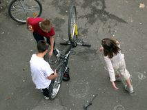 Preparing the bicycle. Children working on his bicycle royalty free stock image