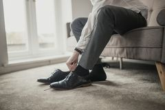 Preparing for a Big Day. Unrecognisable person adult male sitting on a sofa in a domestic room tying his shoelaces Stock Photography