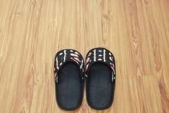 Preparing black slipper on wooden floor Stock Images