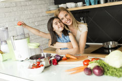 Preparing and blending smoothie. Mother and daughter preparing and blending smoothie from fresh fruits in the modern kitchen royalty free stock photo