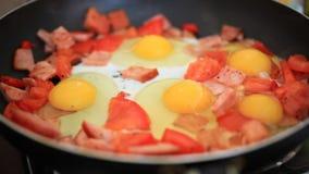 Preparing breakfast of eggs, ham, hot peppers and stock video