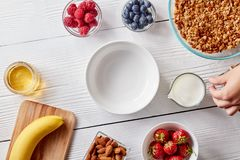 Ripe berries, granola, nuts, honey and an empty plate on a white wooden table. A woman`s hand holds a glass of milk. Preparing breakfast, a woman`s hand holding Royalty Free Stock Images