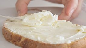 Preparing breakfast. Woman preparing breakfast and spreading cream cheese on bread slice stock video