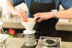 Preparing brewer for a cup of coffee. Closeup of a male barista placing a filter in a coffee brewer while making a cup of coffee in a cafe Stock Photography