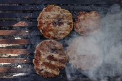 Preparing burger patties on a grill outdoors. Top view Royalty Free Stock Photo