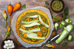 Preparing cauliflower pizza crust with pesto, yellow tomatoes, zucchini, mozzarella cheese and squash blossom Stock Photography