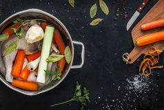 Preparing chicken stock with vegetables (bouillon) in a pot. Black chalkboard as background. Kitchen worktop scenery from above. Layout with free text space Royalty Free Stock Image