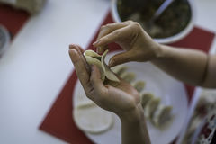 Preparing Chinese Dumplings 3. A close up of a Chinese ladies hands as she prepares traditional, handmade Chinese Dumplings using fresh ingredients stock photo