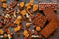 Preparing chocolate. Chocolate bars, nuts, cinnamon on dark wooden background top view.  Stock Photo