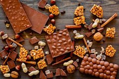 Preparing chocolate. Chocolate bars, nuts, cinnamon on dark wooden background top view Royalty Free Stock Photography
