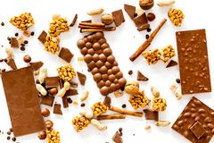 Preparing chocolate. Chocolate bars, nuts, cinnamon on white background top view.  Stock Photos