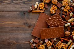 Preparing chocolate. Chocolate bars, nuts, cinnamon on dark wooden background top view copyspace. Preparing chocolate. Chocolate bars, nuts, cinnamon on dark Stock Images