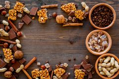Preparing chocolate. Chocolate bars, nuts, cinnamon on dark wooden background top view copyspace. Preparing chocolate. Chocolate bars, nuts, cinnamon on dark Royalty Free Stock Photos