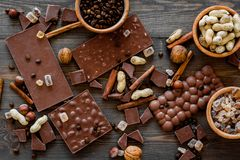 Preparing chocolate. Chocolate bars, nuts, cinnamon on dark wooden background top view.  Royalty Free Stock Photography