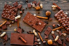 Preparing chocolate. Chocolate bars, nuts, cinnamon on dark wooden background top view.  Stock Images