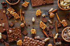 Preparing chocolate. Chocolate bars, nuts, cinnamon on dark wooden background top view.  Stock Image