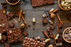 Preparing chocolate. Chocolate bars, nuts, cinnamon on dark wooden background top view Stock Photography