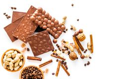 Preparing chocolate. Chocolate bars, nuts, cinnamon on white background top view copyspace. Preparing chocolate. Chocolate bars, nuts, cinnamon on white Stock Images