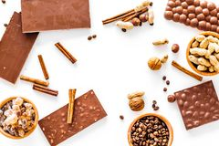 Preparing chocolate. Chocolate bars, nuts, cinnamon on white background top view copyspace. Preparing chocolate. Chocolate bars, nuts, cinnamon on white Royalty Free Stock Image