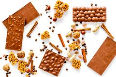 Preparing chocolate. Chocolate bars, nuts, cinnamon on white background top view.  Stock Photo
