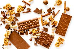 Preparing chocolate. Chocolate bars, nuts, cinnamon on white background top view.  Stock Images