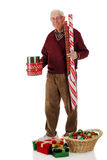 Preparing for Christmas. A senior man carrying gift boxes and wrapping paper as he prepares for Christmas.  On a white background Stock Photos