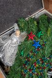 Preparing for Christmas. Artificial tree stored before and after. Xmas. Fairy and decorations stored in an attic storage case Royalty Free Stock Photography