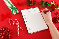 Christmas wish list. Female hand writting in empty notebook with copy space on red messy table background. Preparing for christmas background. Female hand Stock Image