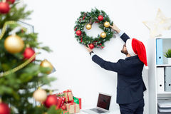 Preparing for Christmas. Businessman in Santa cap hanging coniferous Christmas wreath onto office wall over workplace Royalty Free Stock Photos