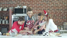 Preparing Christmas cookies. Mother and three children in the kitchen stock video