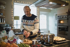 Preparing Christmas Dinner. One mature man is preparing a christmas dinner in the kitchen of his home. He is peeling carrots and parsnips Royalty Free Stock Images