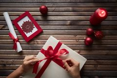 Preparing Christmas gift. Image of female hands tying knot on giftbox surrounded by Christmas symbols Royalty Free Stock Photos