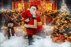 Preparing christmas presents. Portrait of good old Santa Claus holding a sack with gifts on the porch of his decorated house. House of Santa Claus. Christmas and royalty free stock photo