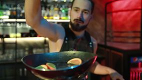 Preparing a cocktail at the bar. The bartender adds sir citrus. Fresh oranges are roasted on the gas ring in the night bar. Slow motion stock video