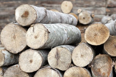 Preparing for cold winter. Wooden logs stack next to a barn wall Stock Image