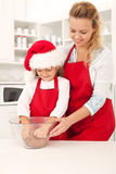 Preparing the cookie dough at christmas time. Preparing the christmas cookie dough - happy girls in the kitchen stock image