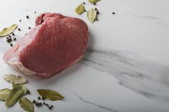 Preparing for cooking in the kitchen.Raw piece of beef and spieces royalty free stock photos