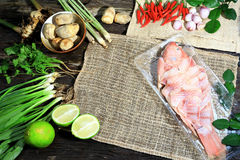 Preparing for cooking Thai spicy and sour soup with the fish, Thai Language is Tom Yum Pha on wooden background. Dark tone Stock Image