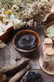 Preparing cosmetic black mud mask in ceramic bowl on vintage wooden background. Front view of facial clay emulsion on table with. Spa products. Natural royalty free stock photos