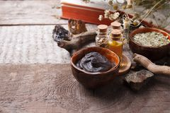 Preparing cosmetic black mud mask in ceramic bowl on vintage wooden background. Front view of facial clay emulsion on table. With spa products. Natural stock photography