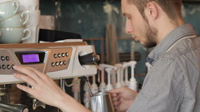 Preparing a cup of coffee with the machine. Handsome male barista making coffee and smiling while standing at the bar counter near the coffee machine. Barista stock footage