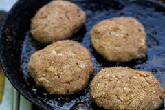 Preparing of cutlet from minced meat in frying pan stock images