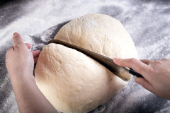 Preparing and cutting pizza dough with knife Royalty Free Stock Photography
