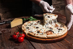 Preparing delicious italian pizza. Master class. Chef lifting slice of hot tasty pizza with melting cheese on rustic wooden table. Italian cuisine, fast food Stock Photography