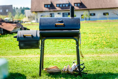 Preparing delicious meat in slow cooking smoker in backyard. Easy to use cylindrical smoker at family backyard barbecue - BBQ picnic stock images