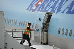 Ground Worker Entering the Korean Air Plane Stock Photo