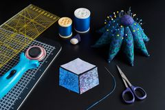 Preparing of diamond pieces of fabrics for sewing quilt. Traditional patchwork, sewing and quilting accessories royalty free stock photography