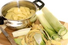 Preparing dinner, Peeling potatoes and leek Royalty Free Stock Photos