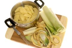 Preparing dinner, Peeling potatoes and leek Royalty Free Stock Photography