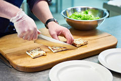 Preparing dishes of fried cheese and green salad Royalty Free Stock Photos